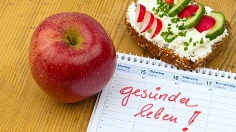"""Apfel und ein Glaswasser neben einem Kalender, auf den """"gesund leben!"""" notiert ist"""