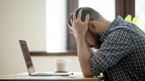 Mann sitzt vor einem Laptop und schlägt die Hände über den Kopf