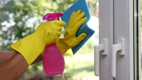Eine Frau putzt mit gelben Gummihandschuhen eine Fensterscheibe
