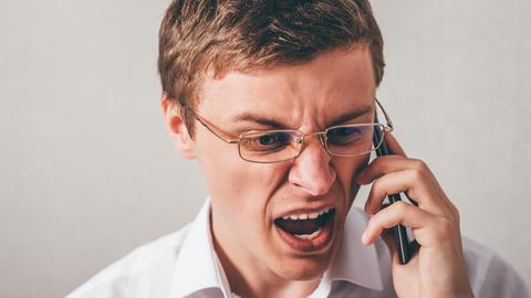Mann schimpft am Smartphone