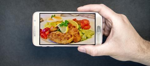 Bild eines Schnitzel mit Pommes auf einem Smartphone