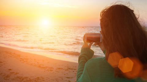 Eine Frau fotografiert am Strand einen Sonnenuntergang mit dem Smartphone