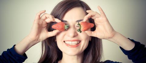 Eine Frau hält sich Erdbeeren vor die Augen