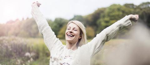 Eine Frau steht in einem Feld und reißt die Arme vor Freude hoch.