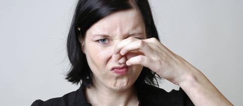 Frau hält sich die Nase zu