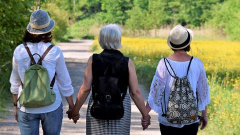 Drei Frauen halten sich an den Händen und gehen durch die Natur