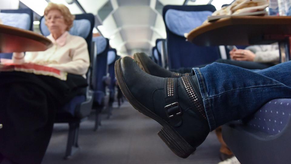 Füße auf dem Sitz im Zug