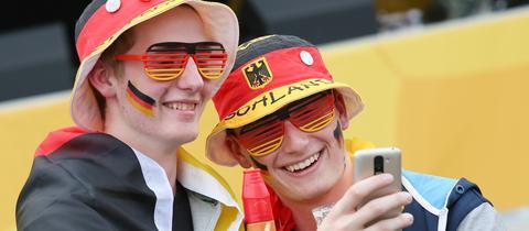 Zwei junge Männer in deutschen Fan-Utensilien machen ein Selfie