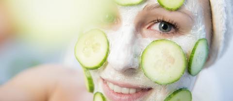 Eine Frau mit Gesichtsmaske und Gurkenscheiben