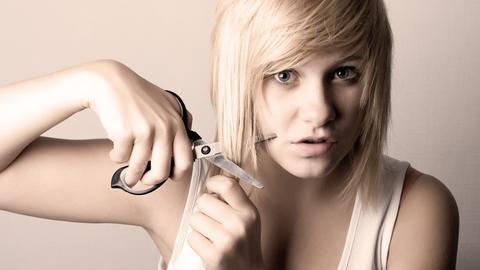 Eine Frau schneidet sich selbst die Haare