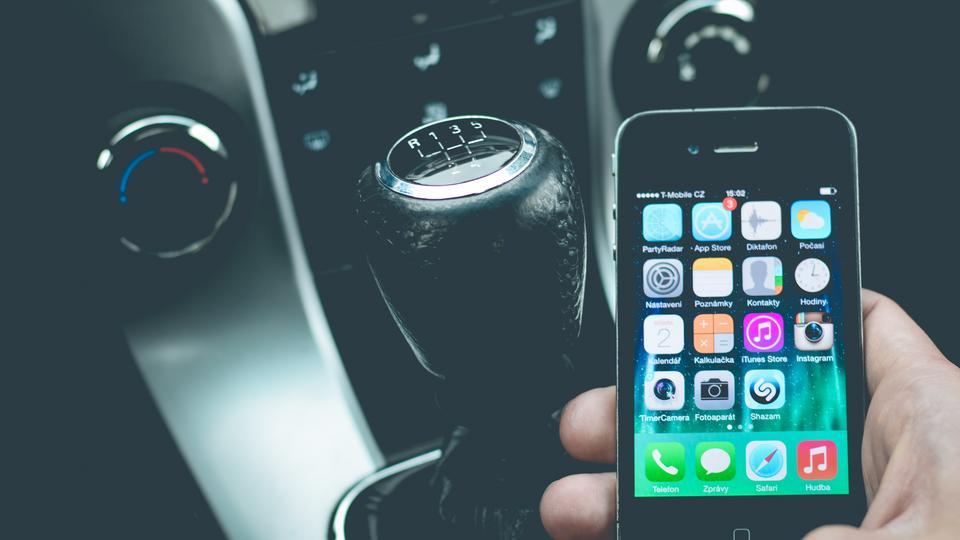 Jemand spielt mit dem Smartphone im Auto