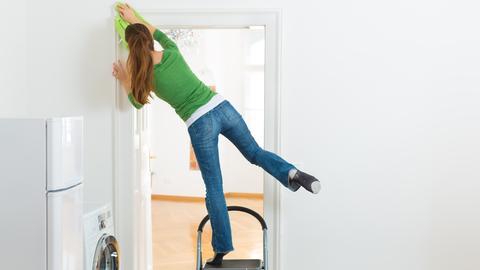 Frau steht auf einer Trittleiter und lehnt sich zum Putzen eines Türrahmens weit nach links.