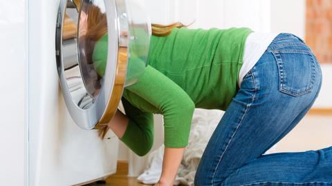 Eine Frau schaut in eine Waschmaschine