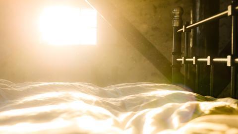 Durch ein Fenster fällt Licht und man sieht den Staub über dem Bett
