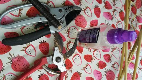 Wickeldraht, Zwickscheren, Haarspray und Äste auf einem Tisch