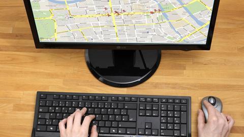 Frau sitzt vor einem Monitor und schaut auf die Karte eines Kartendienstes