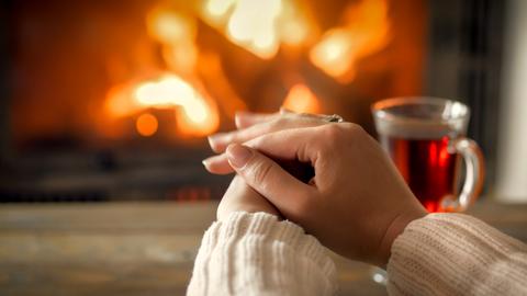 Hände vor einem Kaminfeuer mit einer Tasse Tee