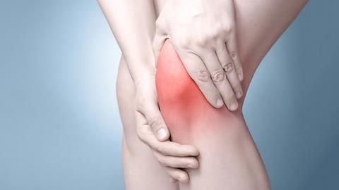 Hände greifen an ein verletztes Knie