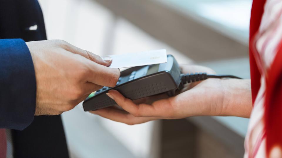 Ein Mann zahlt mit seiner Karte an einem Lesegerät ohne seine Karte einzustecken