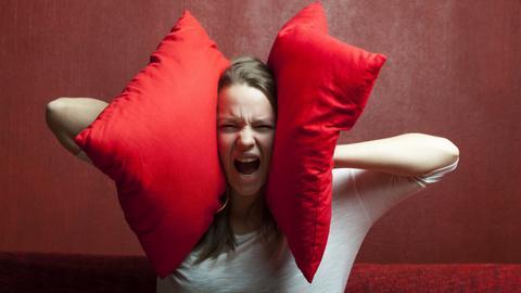 Eine Frau hält sich mit zwei großen, roten Kissen die Ohren zu