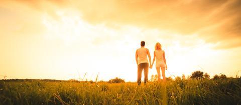 Paar blickt Hand in Hand in die Zukunft