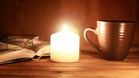 Buch, Kaffeetasse und Kerze