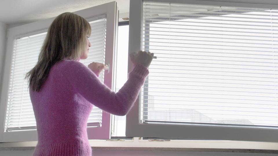 Frau öffnet zwei Fenster