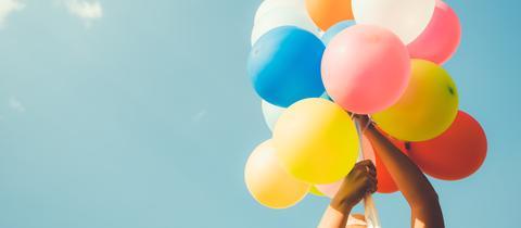Eine Frau hält ein Bündel Luftballons