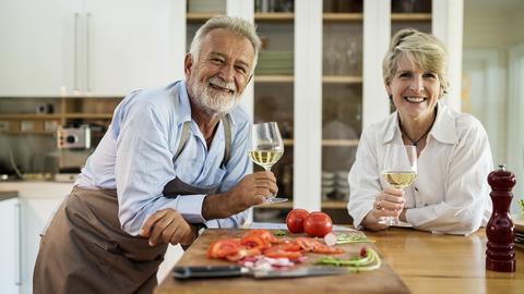 Mann und Frau in der Küche mit Weißwein in der Hand