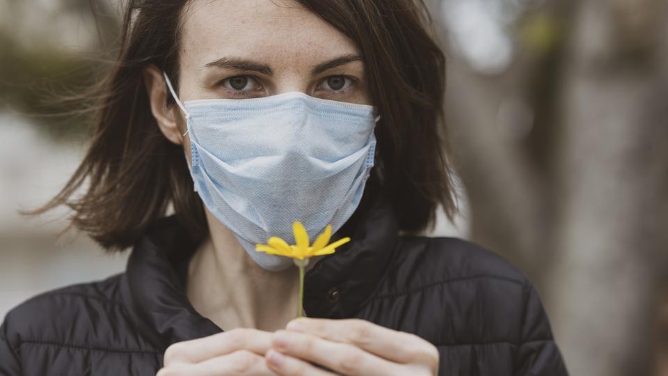 Frau mit Corona-Maske und einer Blume