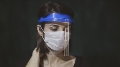 Ausbreitung von Aerosolen verhindern - Frau mit Mund-Nasen-Maske und Gesichtsvisier