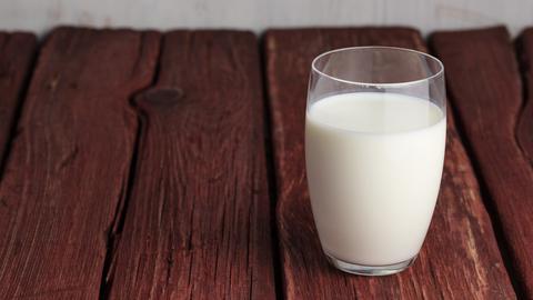 Ein Glas Milch auf einem Holztisch
