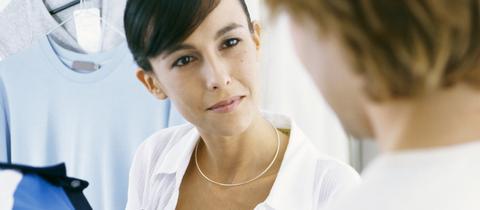 Eine Verkäuferin zeigt einer Kundin ein Kleidungsstück