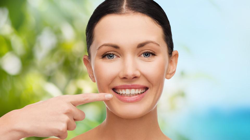 Junge Frau zeigt mit dem rechten Zeigefinger auf die Zähne in ihren leicht geöffneten Mund
