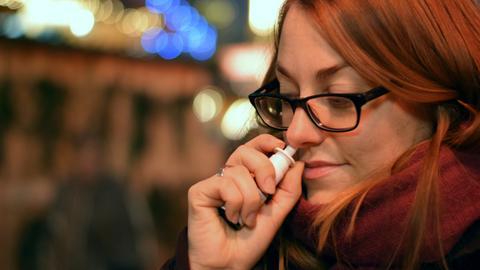 Junge Frau benutzt Nasenspray