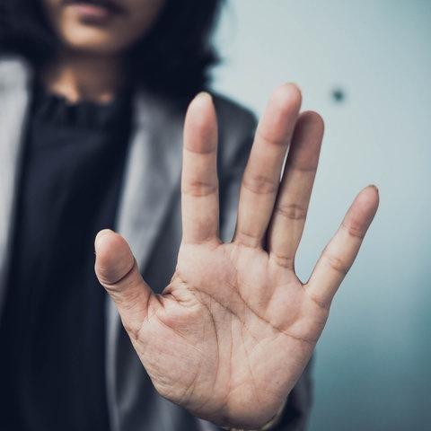 Eine Frau hält ihre Hand in Abwehrhaltung