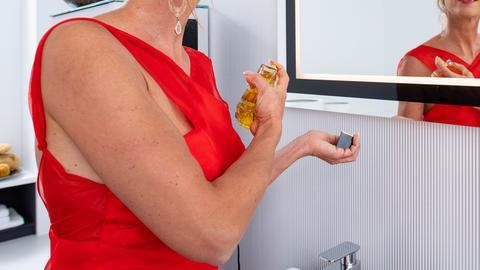Frau steht vor einem Spiegel und besprüht sich mit Parfüm