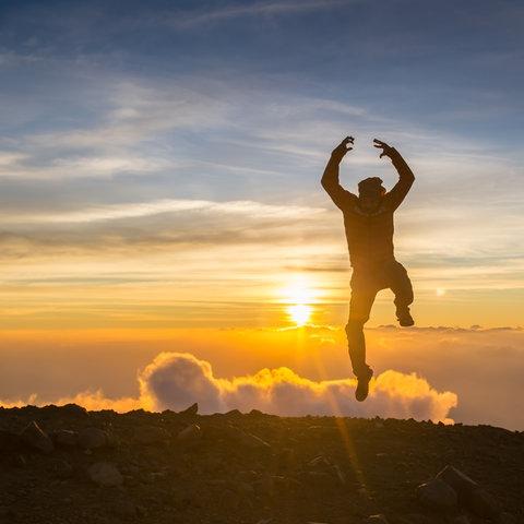 Ein Mann springt im Sonnenuntergang