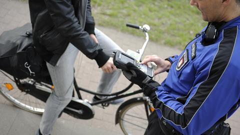 Ein Polizist schreibt eine Radfahrerin auf