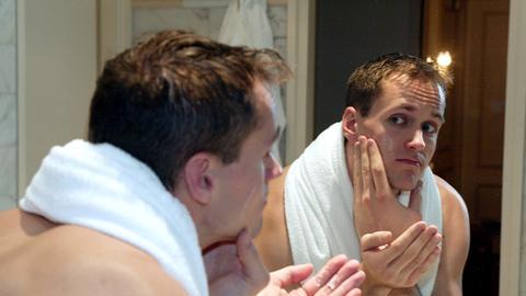 Mann steht vorm Spiegel und reibt sich Rasierwasser ins Gesicht