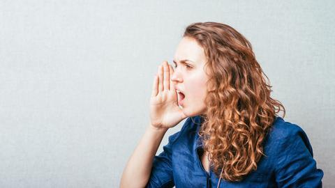 Frau hält die rechte Hand an den Mund und ruft