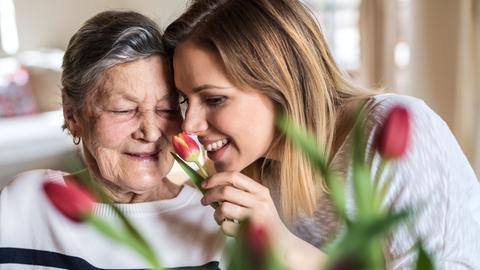 Eine ältere und eine jüngere Frau riechen an einer Tulpenblüte