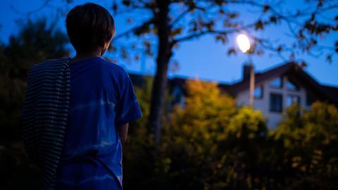 Ein Junge im Schlafanzug steht nachts mit einer Decke im Garten.