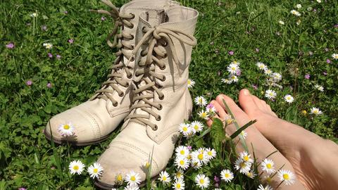 Frau hat auf der sommerlichen Wiese die Stiefel ausgezogen