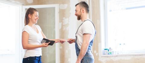 Frau gibt einem Mann in Arbeitskleidung Geld