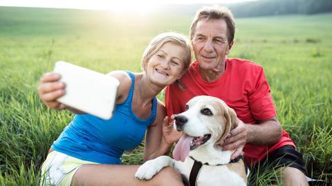 Eine Frau und ein Mann machen mit ihrem Hund ein Selfie