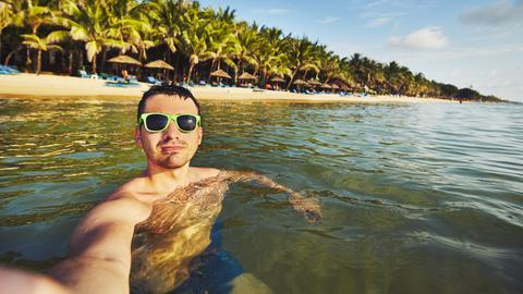 Ein Mann fotografiert sich im Wasser mit Hilfe eines Selfiesticks vor Strand und Palmen
