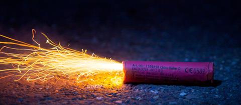 Ein Silvester-Knaller mit brennender Lunte liegt auf dem Boden