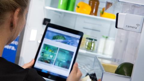 Eine junge Frau schaut sich auf einem iPad das Bild einer im Kühlschrank installierten Kamera an
