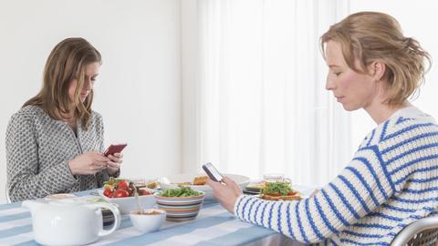 Zwei Frauen sitzen am Esstisch und gucken jeweils auf ihr Handy.